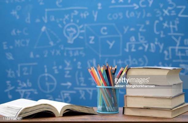 back to school supplies. books and blackboard on wooden background - stipendium stock-fotos und bilder