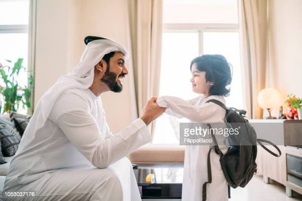 back to school time: arab dad saying hello to his son - back to school stock pictures, royalty-free photos & images