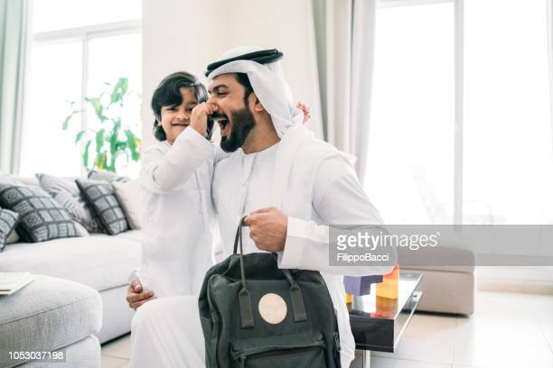 back to school time: arab dad saying hello to his son - gulf countries stock pictures, royalty-free photos & images