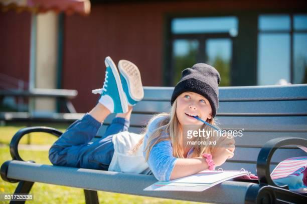 Regreso a la escuela con chica bonita rubia estudiante haciendo la tarea en un parque de Banco