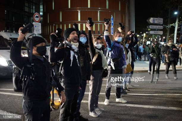 Back turned to riot police, Photographers raise their camera in defiance of the 'Global Secutity Law'. Thousands of protesters took to the streets...