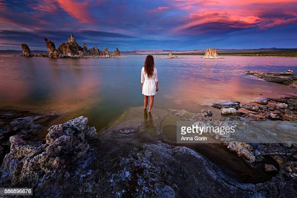 Back view at sunset of barefoot woman in white dress at Mono Lake shoreline at South Tufa, central California