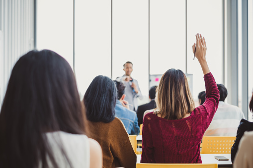Back view business woman raising hand for asking speaker for question and answer concept in meeting room for seminar 1035507788