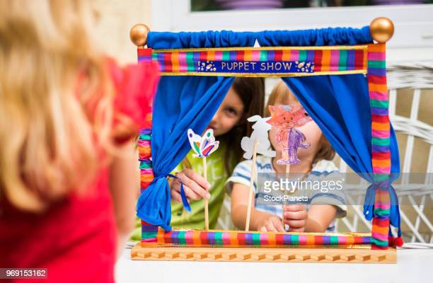 back view girk looking puppet show that play her brother and sister - puppet show stock photos and pictures