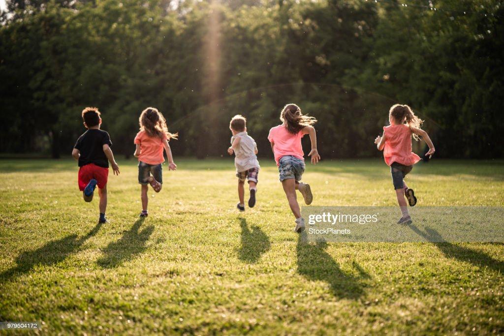 Gruppo di bambini in vista posteriore che corrono nella natura : Foto stock