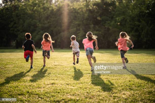 back view group of children running in nature - giochi per bambini foto e immagini stock