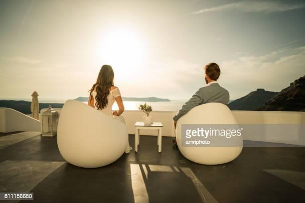 couple de jeunes mariés de vue arrière assis sur la terrasse avec vue sur la caldeira au coucher du soleil