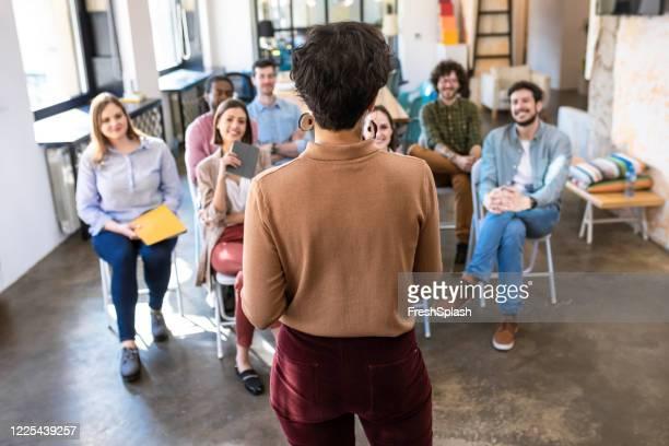 visão de trás de um coach de negócios dando uma palestra para empresários que participam de uma sessão de treinamento - attending - fotografias e filmes do acervo
