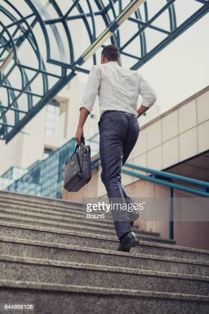 Rücken Ansicht eines Geschäftsmann bewegen Sie die Treppen.