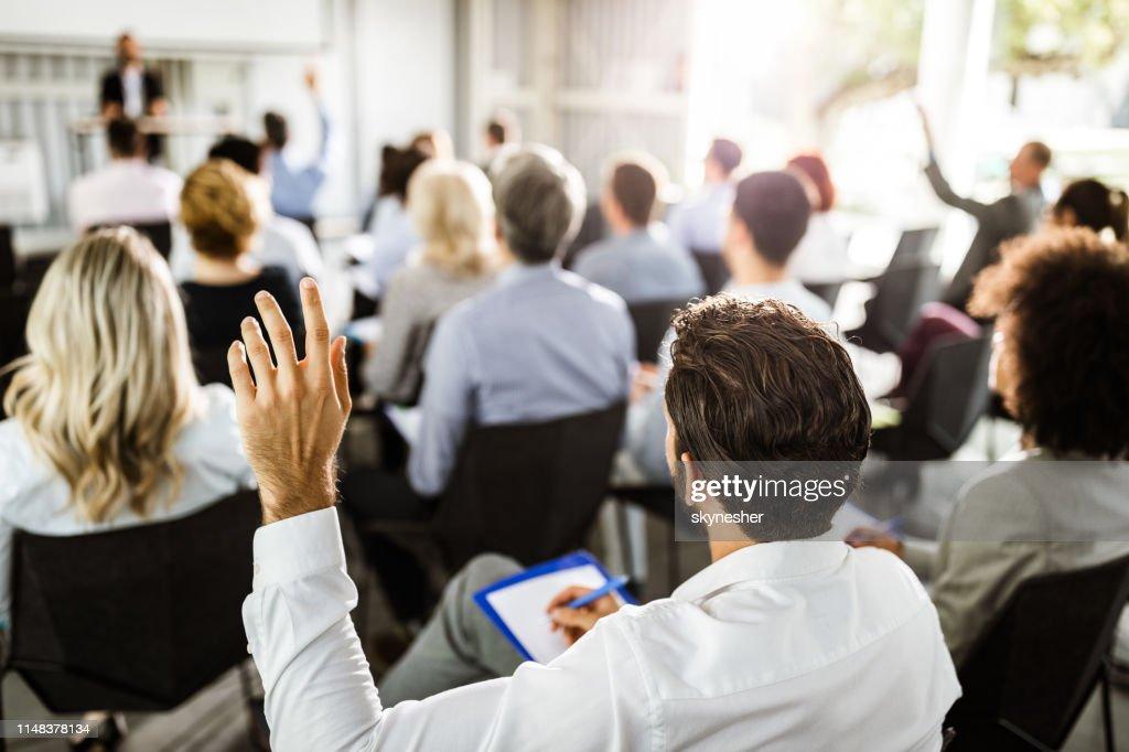 セミナーで手を上げているビジネスマンのバックビュー。 : ストックフォト