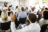 Back view of a businessman raising his hand on a seminar.