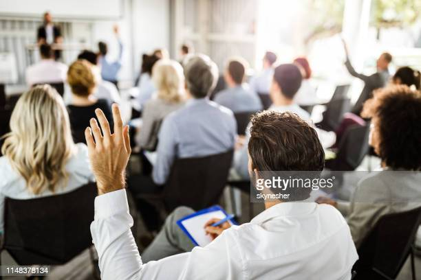 back view of a businessman raising his hand on a seminar. - seminario riunione foto e immagini stock