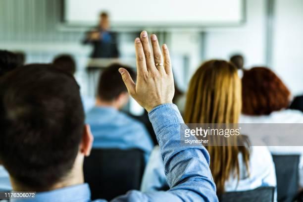 rückblick auf einen geschäftsmann, der auf einem seminar die hand hebt. - antworten stock-fotos und bilder