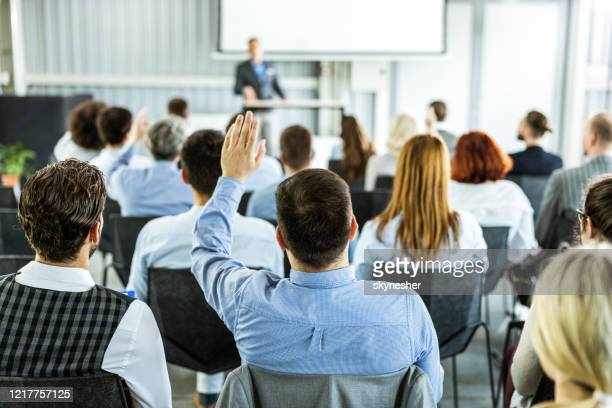 back view of a businessman raising his hand on a seminar. - q and a stock pictures, royalty-free photos & images