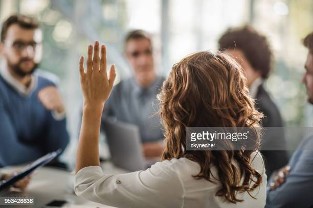 Back view of a businesswoman asking a question on a meeting.