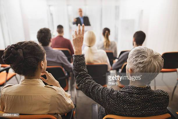 back view of a businesswoman asking a question on seminar. - attending stock pictures, royalty-free photos & images