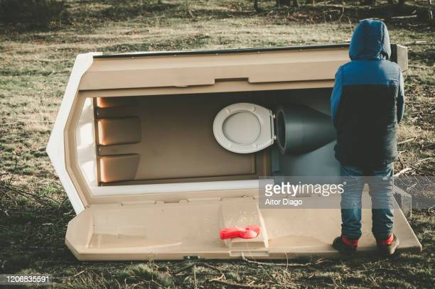 back view of a child  next to a portable toilet fallen on the ground in winter time. - kids peeing stock pictures, royalty-free photos & images