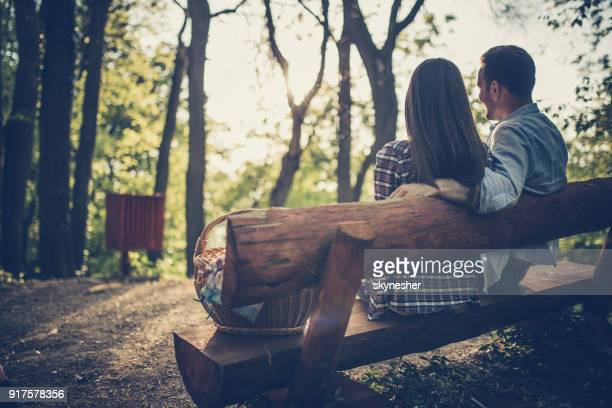 Back view of a couple relaxing on a bench in the forest.
