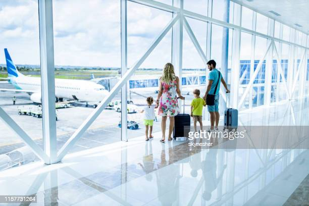 back view of a family looking through window at airport hallway. - airport stock pictures, royalty-free photos & images