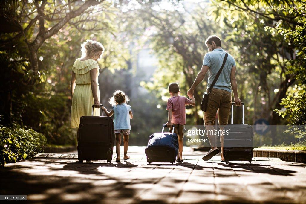 Vue de dos d'une famille tirant leurs valises dans la nature. : Photo