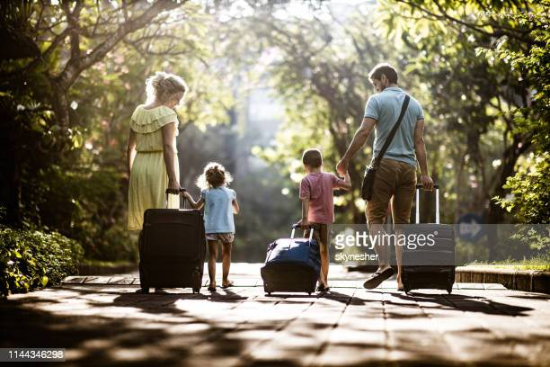 back view of a family pulling their suitcases in nature. - leaving stock pictures, royalty-free photos & images