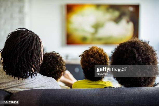 achteraanzicht van een familie tv kijken in de woonkamer. - televisie kijken stockfoto's en -beelden