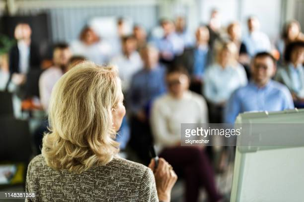 back view of a female speaker talking on business seminar in board room. - presenter stock pictures, royalty-free photos & images