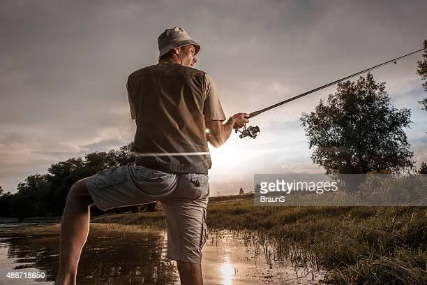 Rückansicht des fisherman Köder Auswerfen der Angel.