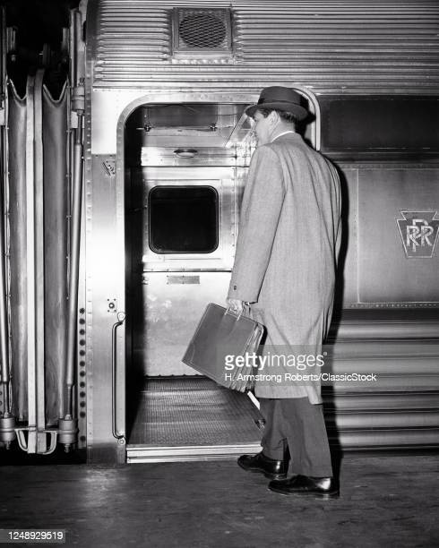 Back View Of A Man Businessman Carrying Leather Briefcase Wearing Top Coat And Hat Commuter Boarding Passenger Train