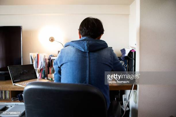 back view of a man concentrating on telecommuting - 後ろ姿 ストックフォトと画像