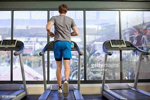 Back view of a man running on a treadmill