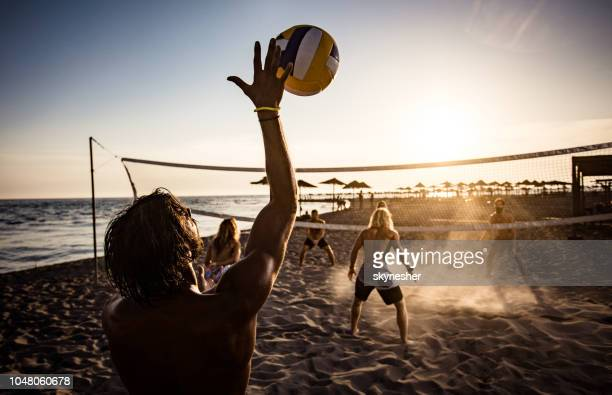 rückansicht eines mannes während des beach-volleyball bei sonnenuntergang. - strandvolleyball spielerin stock-fotos und bilder