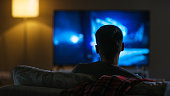 Back View of a Man Sitting on a Couch Watching Movie on His Big Flat Screen TV.