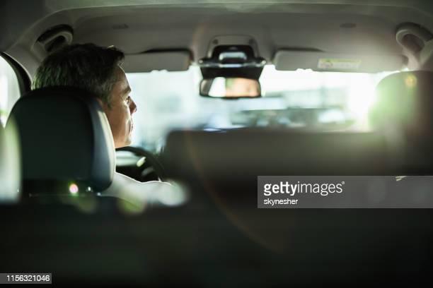 車を運転する中年の成人男性のバックビュー。 - 試運転 ストックフォトと画像