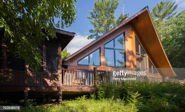 Back view of a milled cottage style flat log profile home with elevated wooden deck and landscaping in summer, Mt-Tremblant, Quebec, Canada