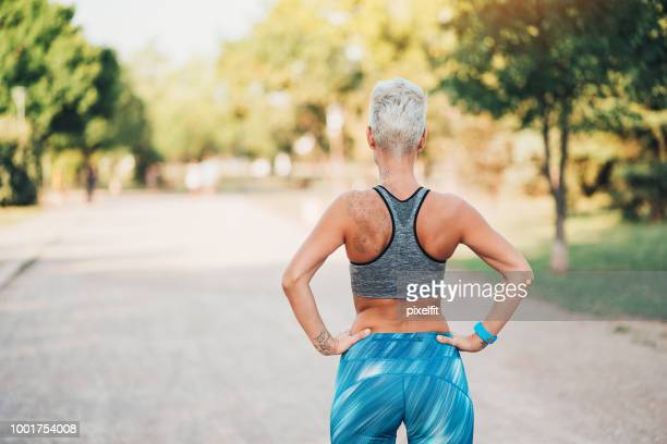 back view of a muscular sportswoman - buttock stock pictures, royalty-free photos & images