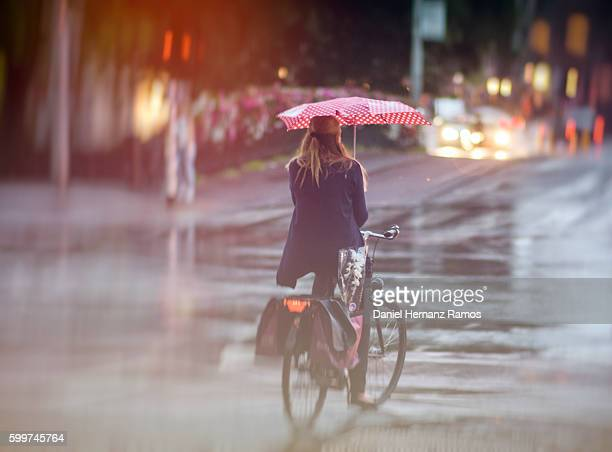 Back view of a woman bicycling in the rain with a red umbrella in Amsterdam city.