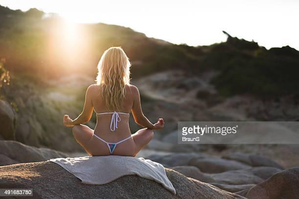 vista posterior de una mujer el ejercicio de yoga on a rock. - tanga fotografías e imágenes de stock