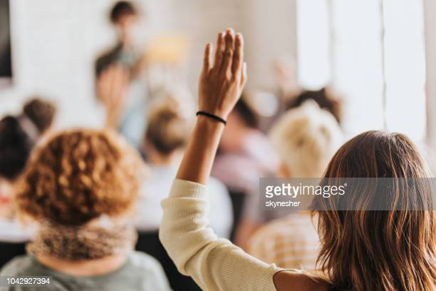 back view of a woman raising her arm on a seminar. - attending stock pictures, royalty-free photos & images