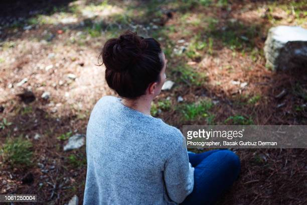 back view of a woman sitting in the forest peacefully - basak gurbuz derman stock photos and pictures