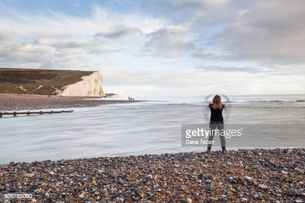 Back view of a woman standing at beach where the river Cuckmere floats into the sea with white cliffs in the background