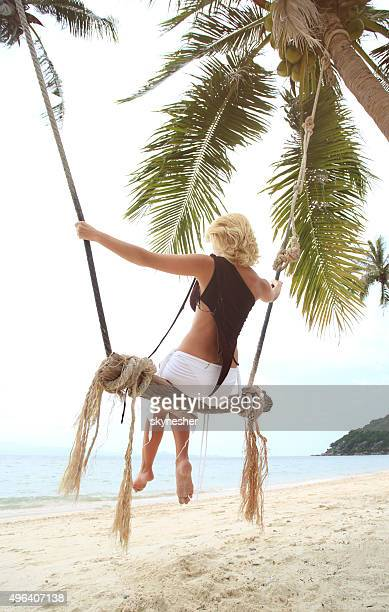 Back view of a woman swinging at the beach.