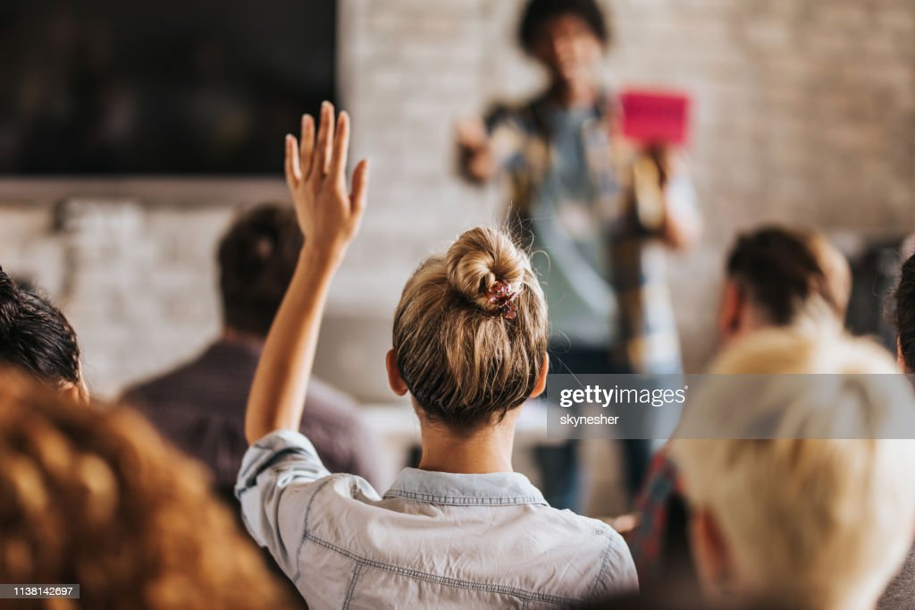 Back view of a woman wants to ask a question on a seminar. : Stock Photo