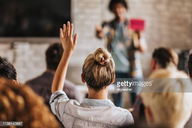back view of a woman wants to ask a question on a seminar. - casual clothing stock pictures, royalty-free photos & images