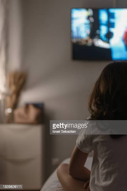 back view of a young caucasian girl sitting on her bed while watching television. - unrecognisable person stock pictures, royalty-free photos & images