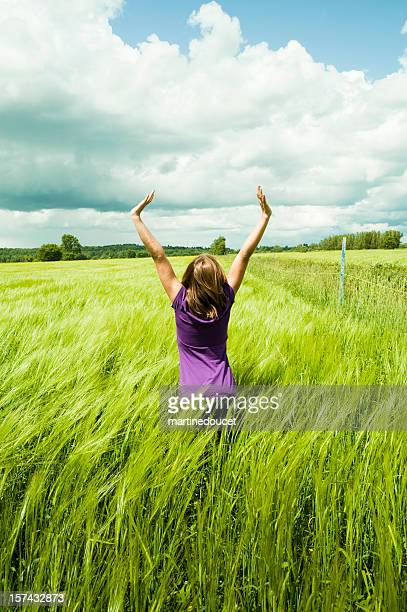 Back View of a young girl enjoying nature in a wheat field