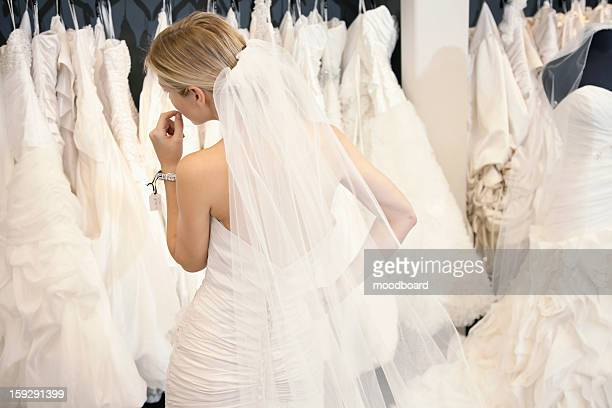 back view of a young woman in wedding dress looking at bridal gowns on display in boutique - robe de mariée photos et images de collection