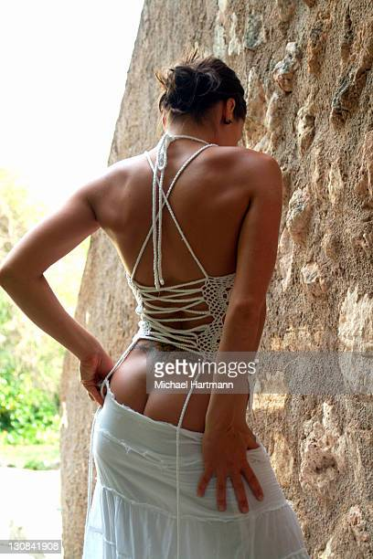 back view of a young woman with white laced top and white skirt, majorca, spain - female bare bottoms stock photos and pictures