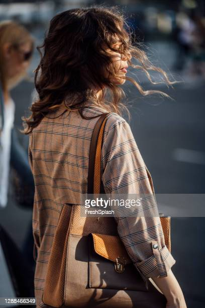 back view of an anonymous women walking around the city - brown purse stock pictures, royalty-free photos & images