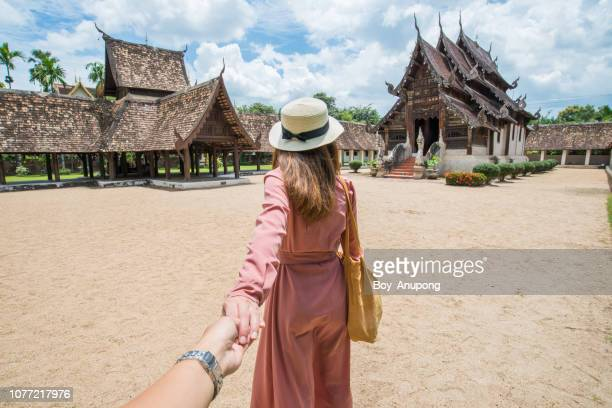 Back view of Asian tourist holding her boyfriend hand and traveling in Wat Inthrawat temple in Chiang Mai, Thailand.
